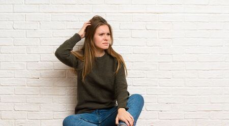 Young woman sitting on the floor having doubts while scratching head