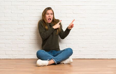 Young woman sitting on the floor frightened and pointing to the side Stockfoto - 128617051