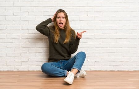 Young woman sitting on the floor surprised and pointing finger to the side