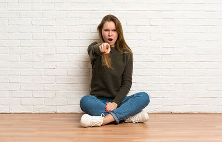 Young woman sitting on the floor surprised and pointing front