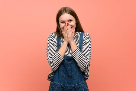 Young woman with overalls over pink wall smiling a lot while covering mouth