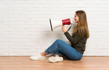 Young woman sitting on the floor shouting through a megaphone Stockfoto - 128617057