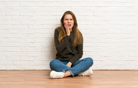 Young woman sitting on the floor with toothache Stockfoto - 128616964