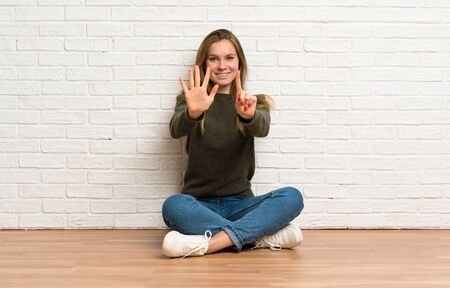 Young woman sitting on the floor counting six with fingers Stockfoto - 128616496