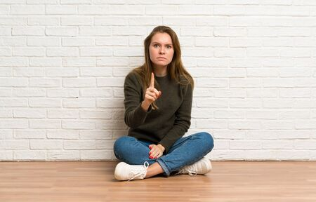 Young woman sitting on the floor frustrated and pointing to the front Stockfoto - 128616498