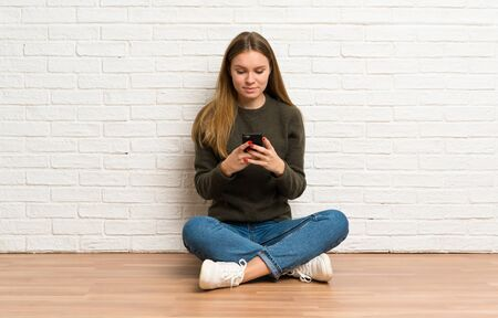 Young woman sitting on the floor sending a message with the mobile Stockfoto - 128616436