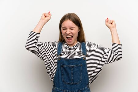 Young woman in dungarees over white wall celebrating a victory