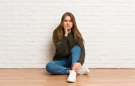 Young woman sitting on the floor having doubts Stock Photo