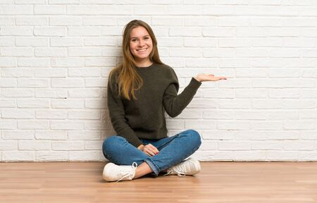 Young woman sitting on the floor holding copyspace imaginary on the palm to insert an ad