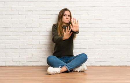 Young woman sitting on the floor nervous stretching hands to the front Stockfoto - 128616326