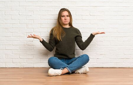 Young woman sitting on the floor unhappy for not understand something Stockfoto - 128616319