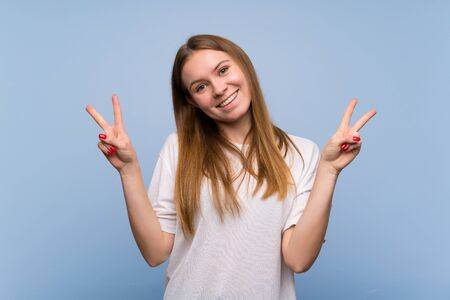 Young woman over blue wall smiling and showing victory sign with both hands Banque d'images - 128616117