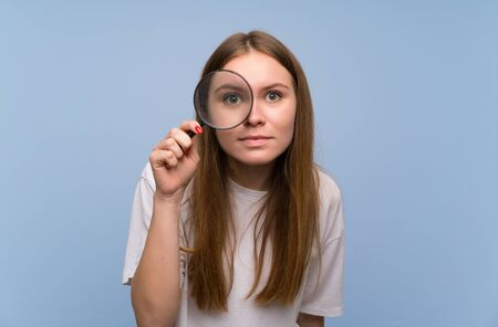 Young woman over blue wall taking a magnifying glass and looking through it