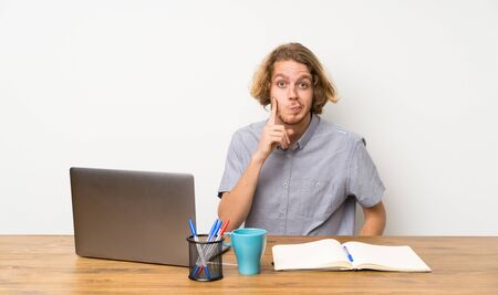 Blonde man with a laptop Looking front