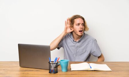 Blonde man with a laptop listening to something by putting hand on the ear
