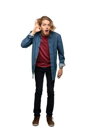 Full-length shot of Blonde man listening to something by putting hand on the ear over isolated white background