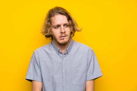 Blonde man over isolated yellow background with confuse face expression Standard-Bild