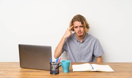 Blonde man with a laptop making the gesture of madness putting finger on the head Stockfoto