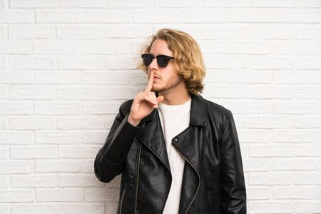 Blonde man with sunglasses doing silence gesture Archivio Fotografico