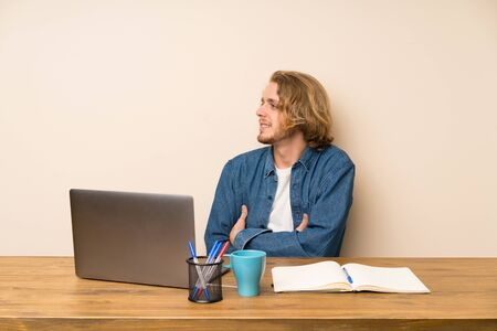 Blonde man with a laptop looking to the side