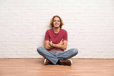 Blonde man sitting on the floor keeping the arms crossed in frontal position