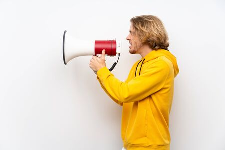 Blonde man with  sweatshirt over white wall shouting through a megaphone