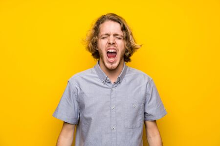 Blonde man over isolated yellow background shouting to the front with mouth wide open