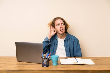 Blonde man with a laptop listening something