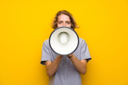 Blonde man over isolated yellow background shouting through a megaphone