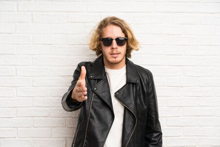 Blonde man with sunglasses handshaking after good deal