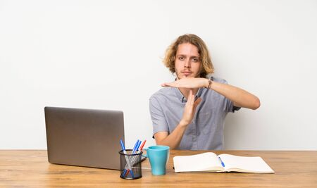Blonde man with a laptop making time out gesture Banco de Imagens