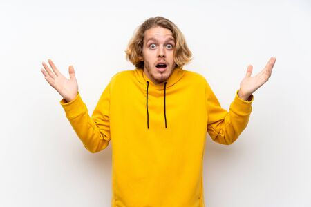 Blonde man with  sweatshirt over white wall with shocked facial expression
