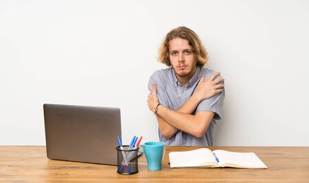 Blonde man with a laptop freezing