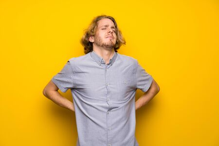 Blonde man over isolated yellow background suffering from backache for having made an effort