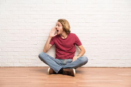 Blonde man sitting on the floor shouting with mouth wide open to the lateral