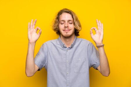 Blonde man over isolated yellow background in zen pose Фото со стока - 128715868