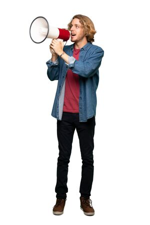 Full-length shot of Blonde man shouting through a megaphone over isolated white background