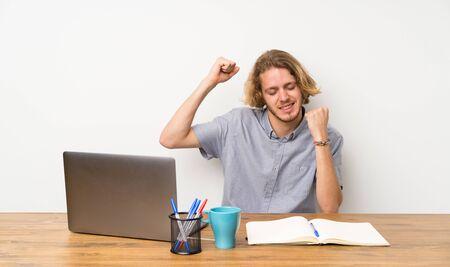 Blonde man with a laptop celebrating a victory Stockfoto