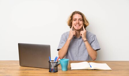 Blonde man with a laptop smiling with a happy and pleasant expression Stock Photo