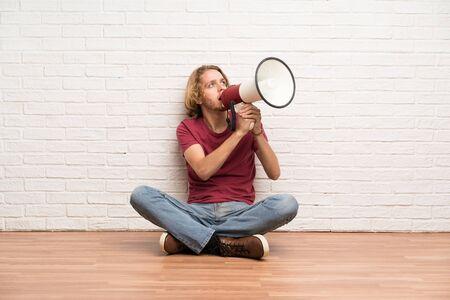 Blonde man sitting on the floor shouting through a megaphone
