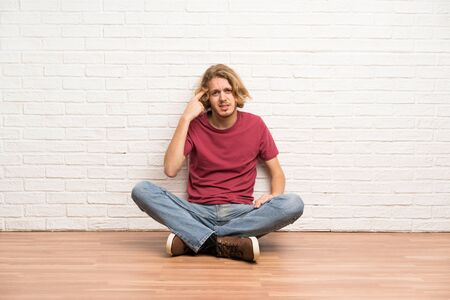 Blonde man sitting on the floor making the gesture of madness putting finger on the head Stockfoto