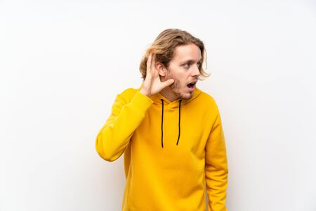 Blonde man with  sweatshirt over white wall listening to something by putting hand on the ear Imagens