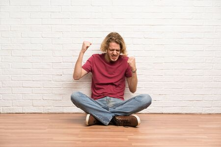 Blonde man sitting on the floor celebrating a victory Stockfoto