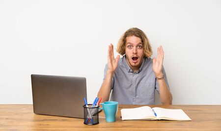 Blonde man with a laptop with shocked facial expression