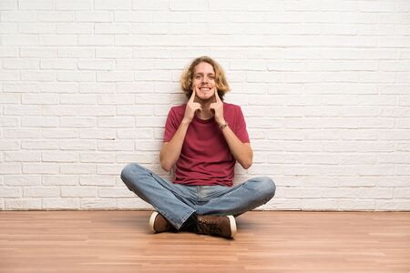 Blonde man sitting on the floor smiling with a happy and pleasant expression Stock Photo