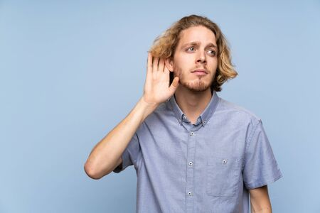 Blonde man over isolated blue wall listening something Imagens