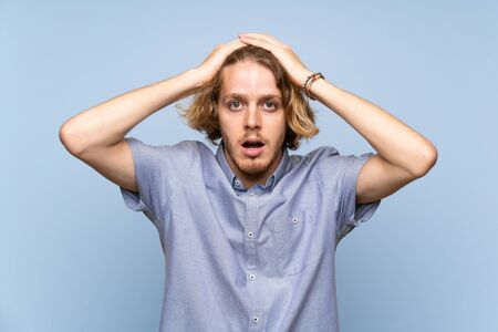 Blonde man over isolated blue wall with surprise facial expression Фото со стока