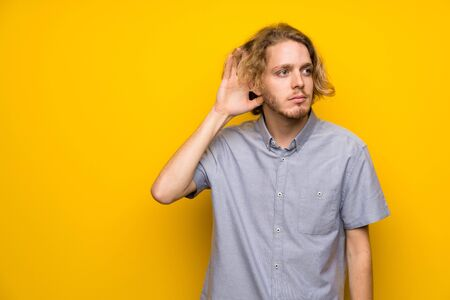 Blonde man over isolated yellow background listening to something by putting hand on the ear