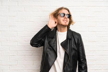Blonde man with sunglasses listening something