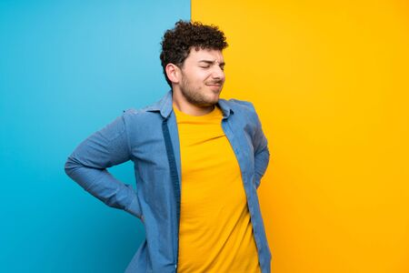 Man with curly hair over colorful wall suffering from backache for having made an effort